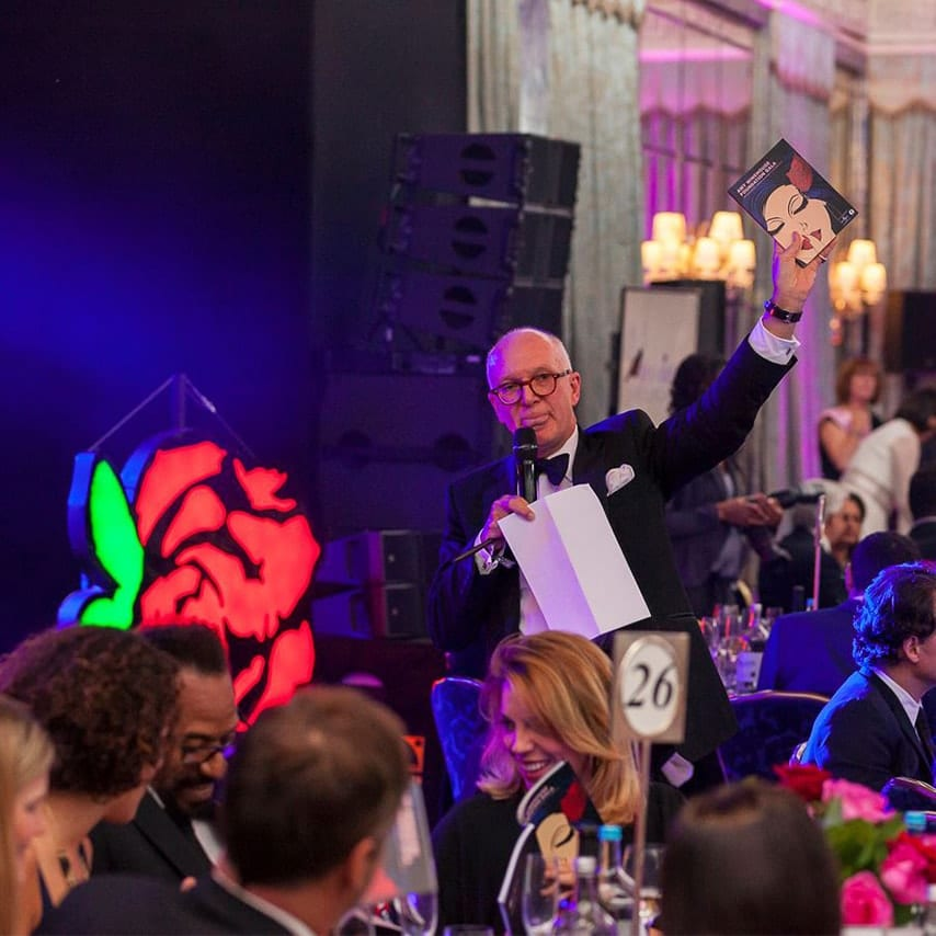 An image of a presenter holding up the brochure at the Amy Winehouse Foundation Gala