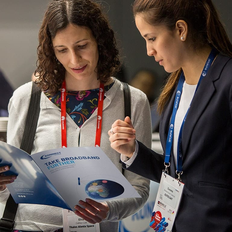 A person discussing the contents of the event brochure with a member of the Konnect team