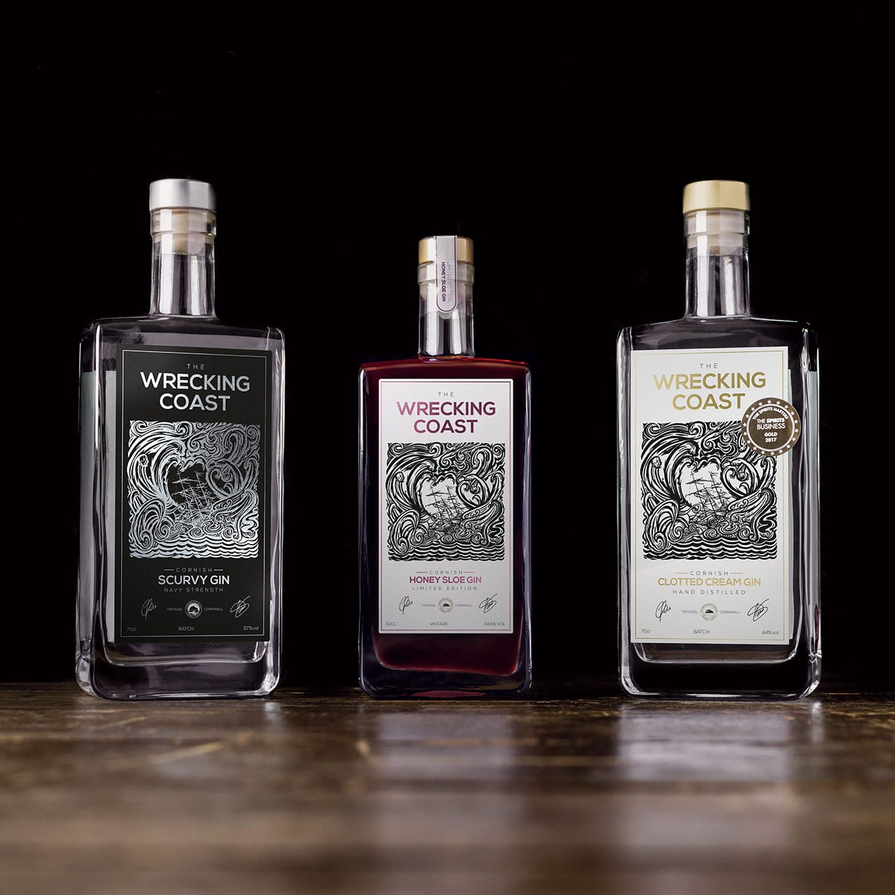The Wrecking Coast Distillery Scurvy gin, Cornish Clotted Cream gin and Honey Sloe gin bottles, photographed on a wooden surface with a black background
