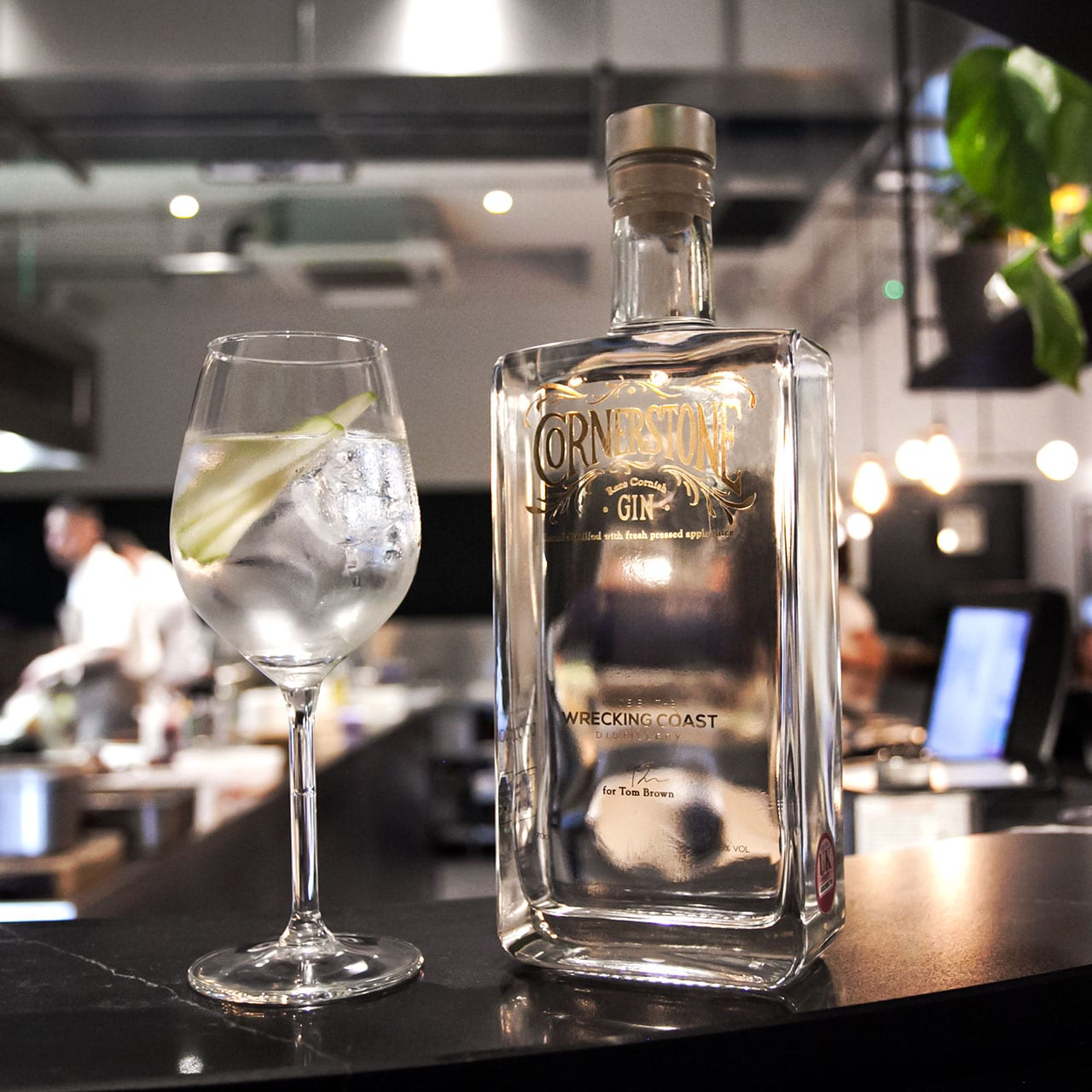 A photograph of the Cornerstone gin bottle with a gin glass on the bar-top at Tom Brown's restaurant Cornerstone Hackney Wick in London