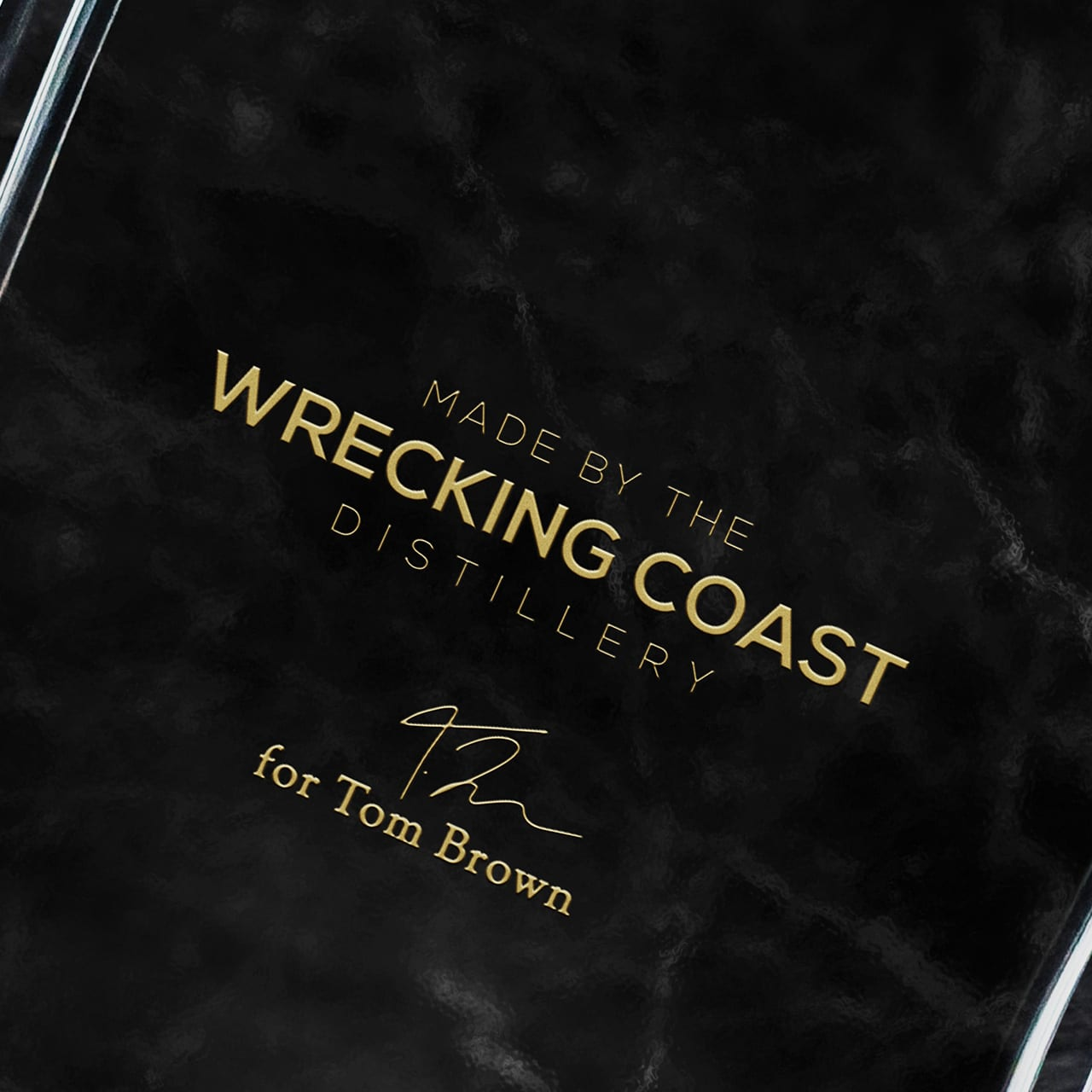 A close-up shot of gin bottle design reading 'Made by the wrecking coast distillery for Tom Brown'