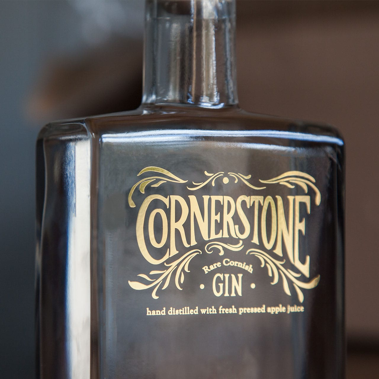 A close-up photograph of the Cornerstone rare Cornish gin bottle gold label design and branding