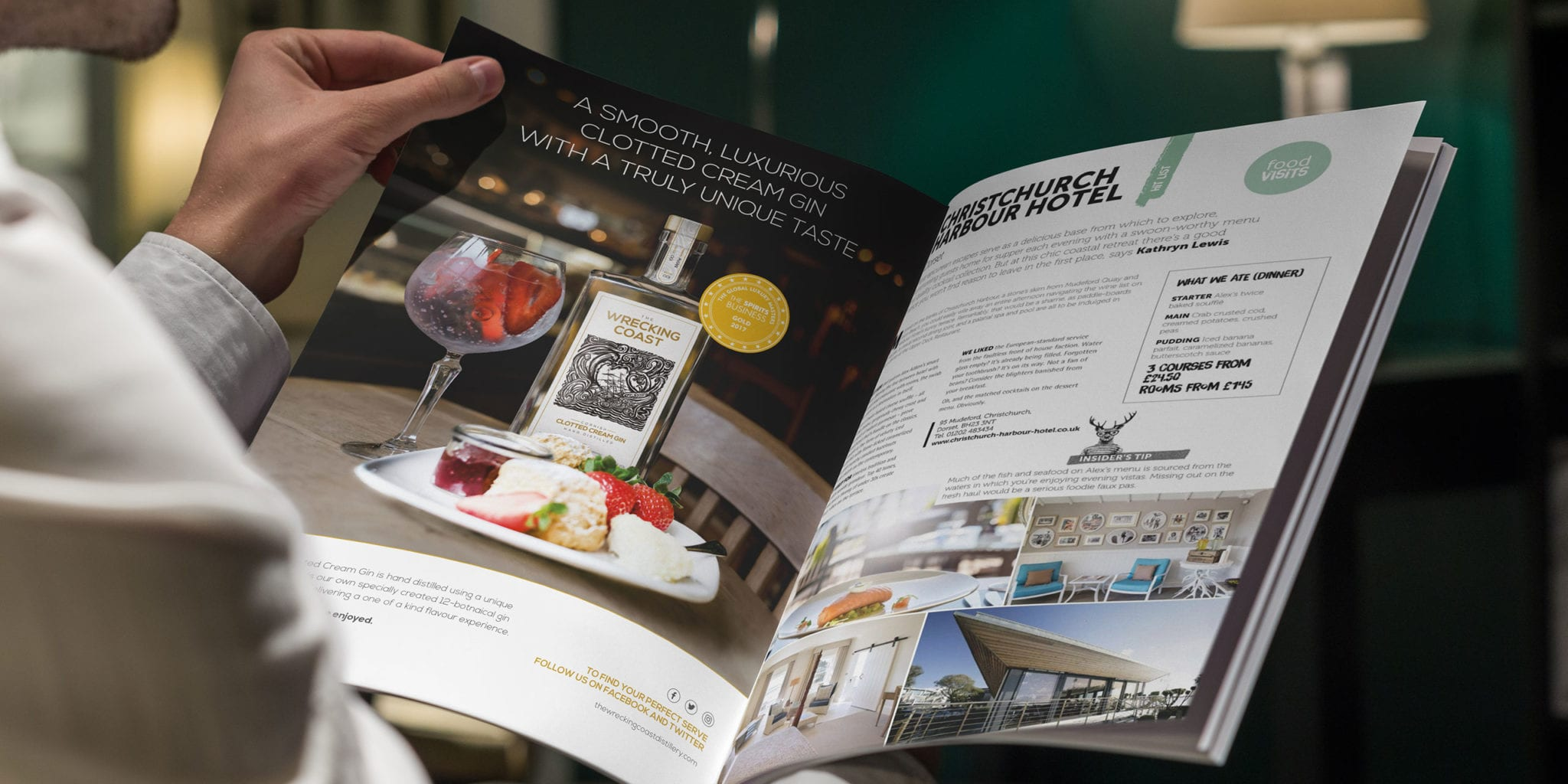 A seated man reading a magazine whilst looking at a Wrecking Coast Distillery advert in a food and spirit magazine